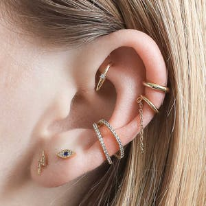 Large ear with multiple piercings wearing products from the Maison Miru Ear Bar