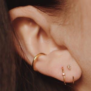 Dewdrop Huggie Earrings in 14k Gold on model
