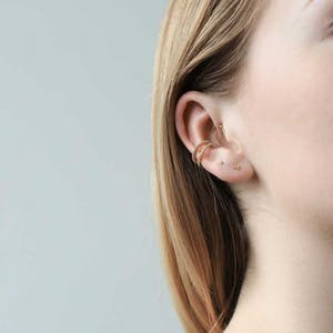 Tiny Trinity Threaded Flat Back Earring in 14k Gold on model