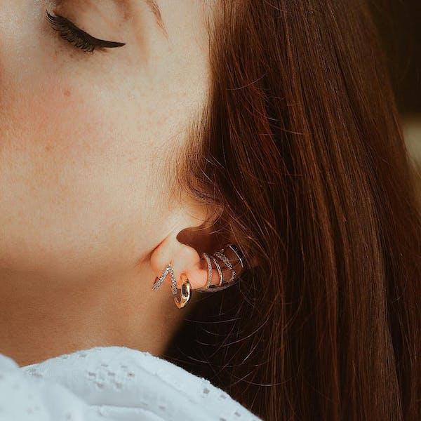 Infinite Huggie Earrings on model