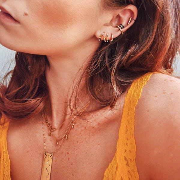 Rainbow Infinite Huggie Earrings on model